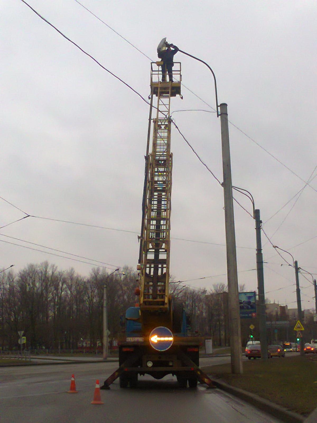 Фото 1. Работа электрика на автовышке - электрик ГУП «Ленсвет» меняет лампу в уличном фонаре на проспекте Стачек (развязка путепровода у съезда по направлению к Петергофскому шоссе).